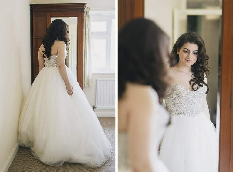 Bride admiring her dress in the mirror.
