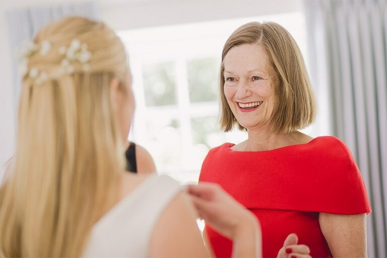 Brides mum looks very happy to see her daughter in her wedding dress.