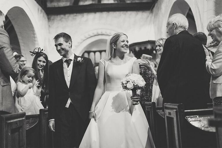 Bride smiles at her grandfather as she walks down the aisle at a church.