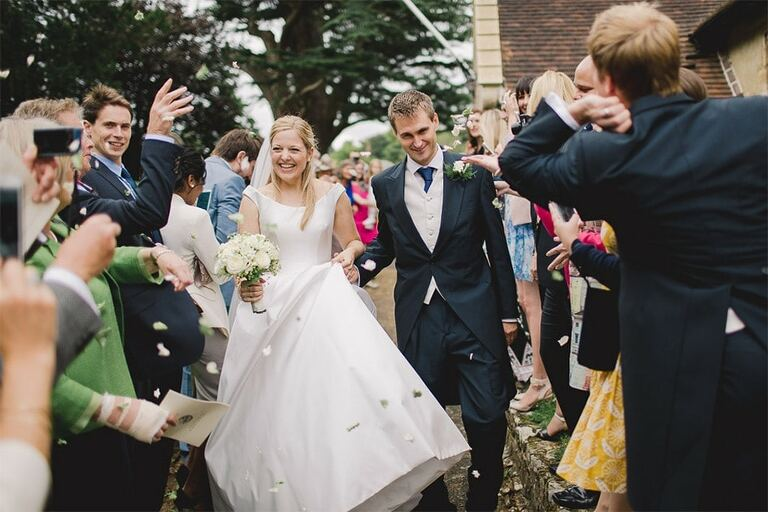 A bride and groom being showered with confetti at their wedding in Surrey.