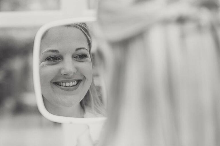 Bride looks in the mirror as she smiles.