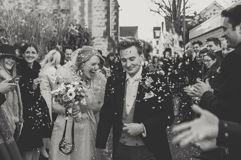 Lots of confetti being thrown at a couple in Nutfield priory wedding venue in Surrey Hills.