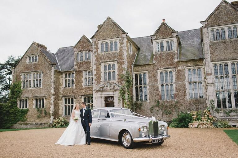 Loseley Park Wedding Photographer in front of the building with the newly married couple.