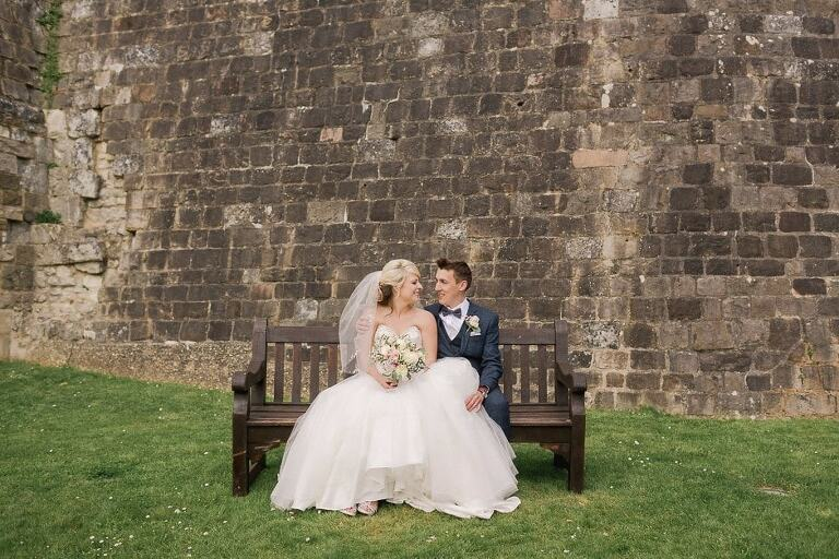 Bride and Groom sitting on a bemch at Farnham Castle in Surrey.