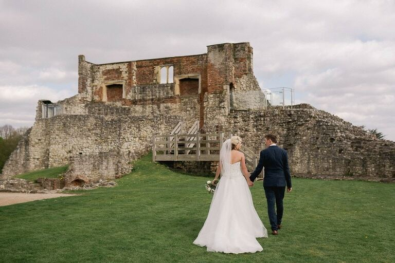 newlyweds take a stroll together at Farnham Castle on the lawn.