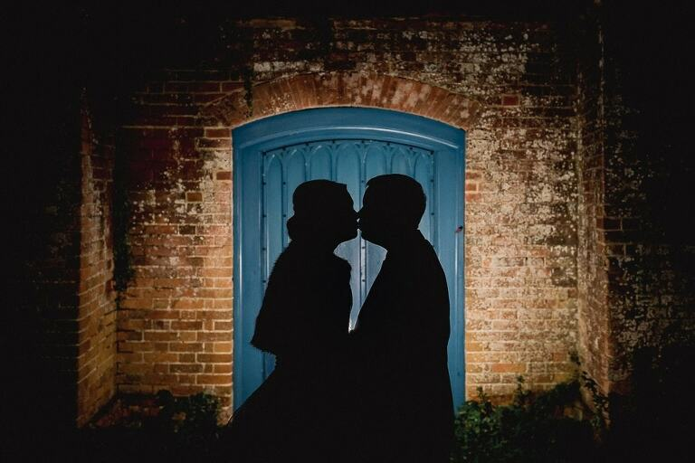 Silhoutted bride and groom at farnham castle wedding venue.