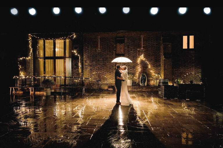 Bride and Groom in the rain at Long Furlong Barn in Sussex