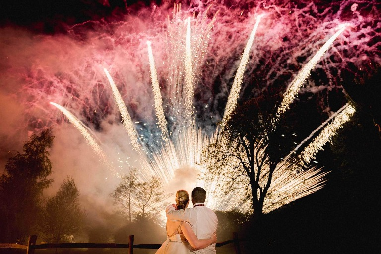 Bride and groom watching platinum fireworks at Coltsford Mill in Surrey