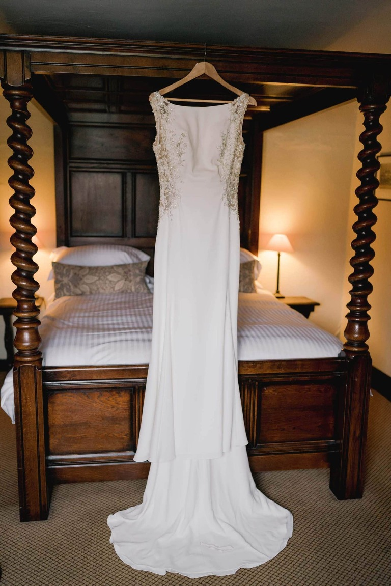 Wedding dress hanging on a four poster bed.