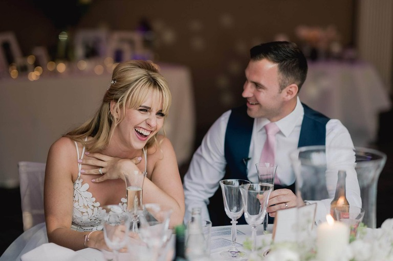 Wedding speeches, the bride is laughing.