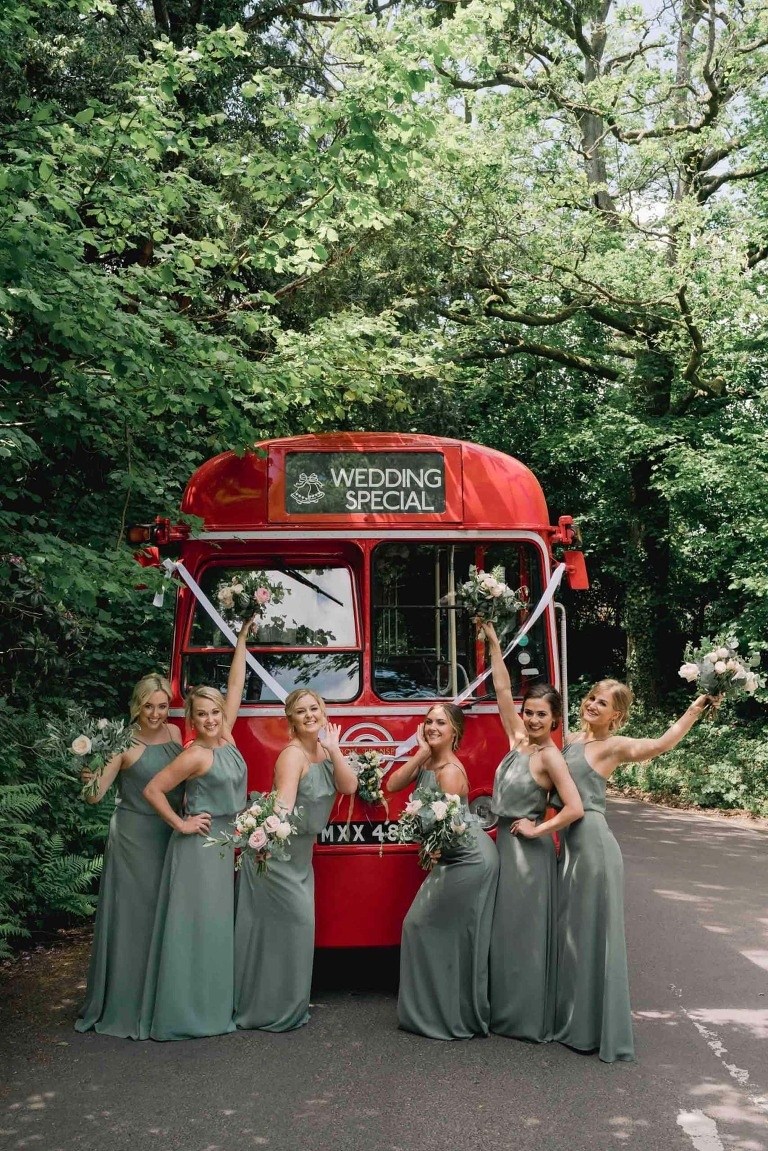 Wedding photography with bridesmaids posing in front of a red doubke decker bus.