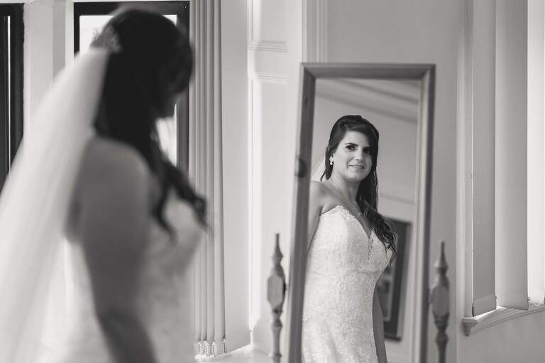 Bride looking in the mirror before the ceremony.
