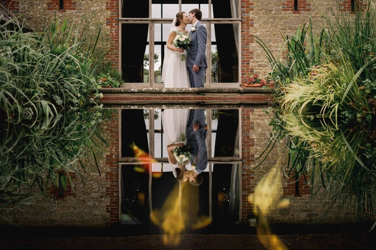 Rustic Wedding couple kissing at Bartholemew Barn in Sussex